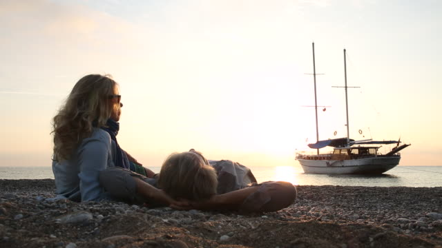couple relax on beach at sunrise, look out to wooden ships - auf der seite liegen stock-videos und b-roll-filmmaterial