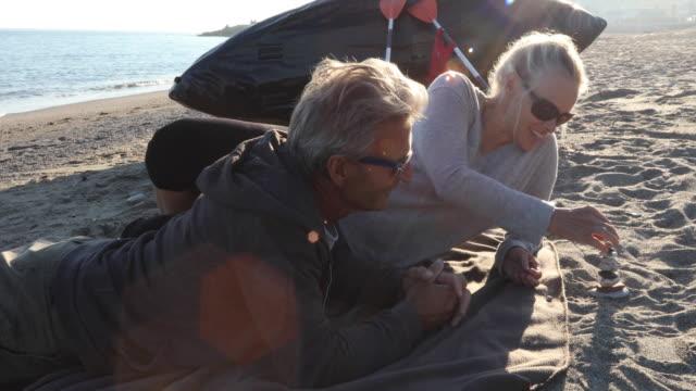Couple relax on beach beside kayak, stacking rocks