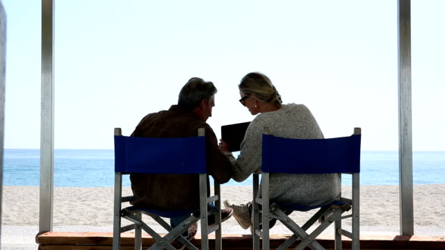 Couple relax on beach chairs with digital tablet, book, at beach