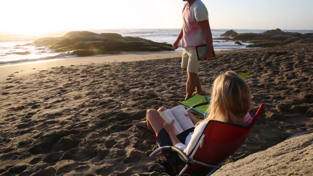 Couple relax on beach nears surf edge, with book and digital tablet