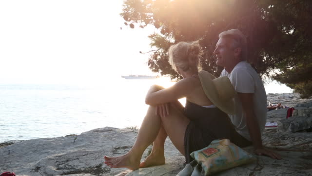 Couple relax on beach rocks, look out to sea