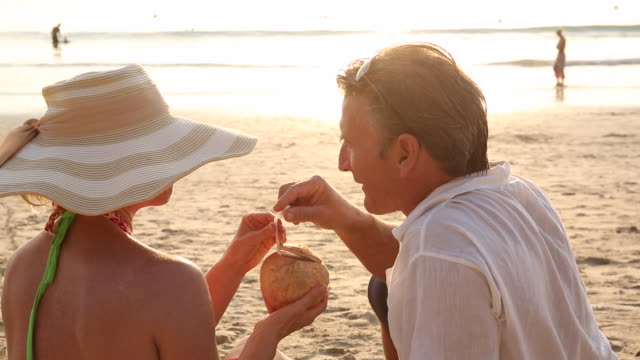Couple relax on beach, woman shares coconut with man