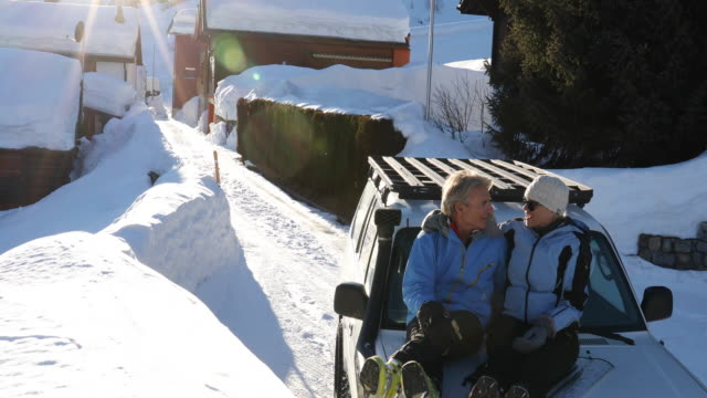 Couple relax on car hood after skiing village