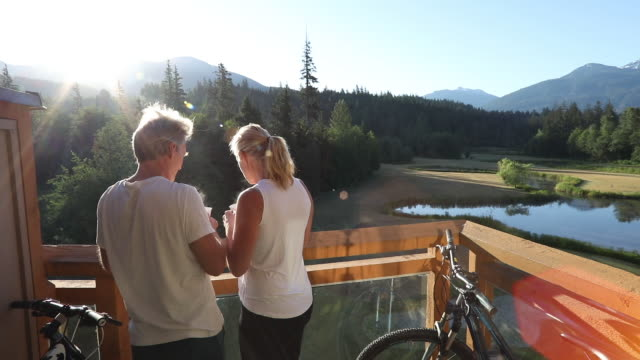 Couple relax on deck at sunrise, look out to mountain scene