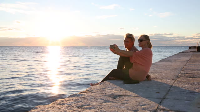 couple relax on flagstone pier, look out to sea - paving stone stock videos and b-roll footage