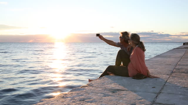 Couple relax on flagstone pier, look out to sea