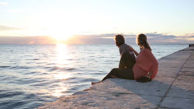 couple relax on flagstone pier, look out to sea - paving stone stock videos & royalty-free footage