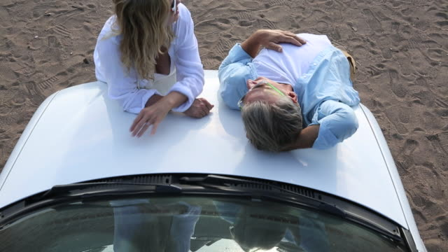 couple relax on hood of car, conversing, beach behind - hood clothing stock videos and b-roll footage