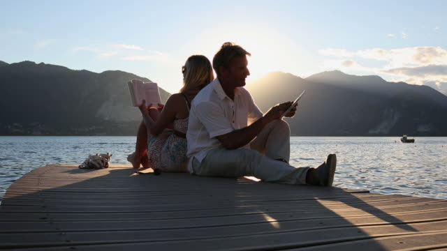 Couple relax on lake pier, he looks at digital tablet, she reads book