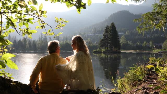 Paar ontspannen op de berg Lakeshore bij zonsopgang
