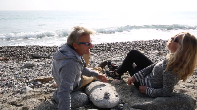 Couple relax on pebble beach, stacking stones, surf behind
