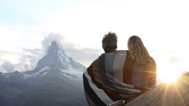 Couple relax on rock ledge, cloaked in blanket