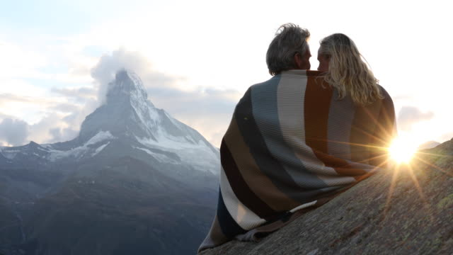 vídeos de stock e filmes b-roll de couple relax on rock ledge, cloaked in blanket - mulheres maduras