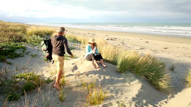 vídeos y material grabado en eventos de stock de couple relax on shoreline dunes - descalzo