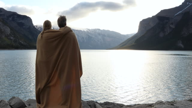 couple relax on shoreline rocks wearing blanket, look out across lake - blanket stock videos & royalty-free footage