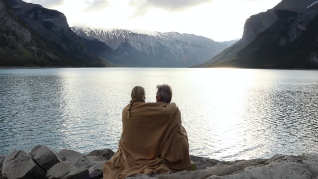 couple relax on shoreline rocks wearing blanket, look out across lake - distant stock videos & royalty-free footage