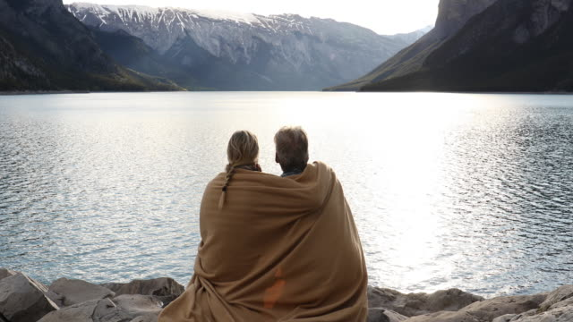vídeos de stock e filmes b-roll de couple relax on shoreline rocks wearing blanket, look out across lake - plano picado
