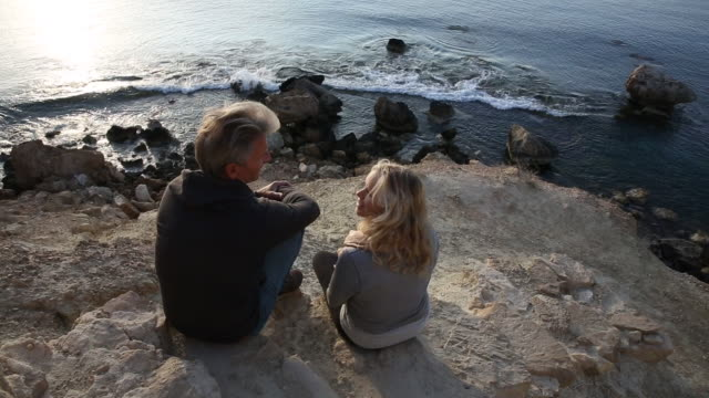 Couple relax on stone pathway above sea, look out to view