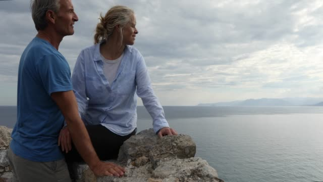 couple relax on stone wall above sea, coastline - stone wall stock videos and b-roll footage