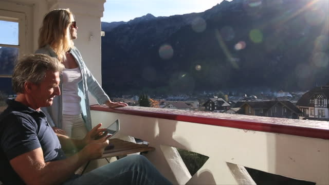 Couple relax on terrace, take digital tablet pic of view