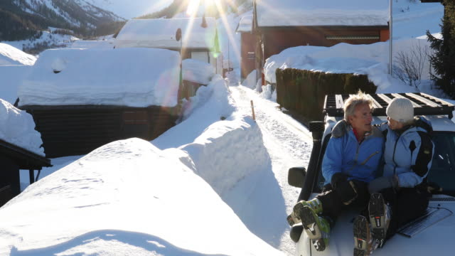Couple relax on vehicle hood after skiing, in Swiss village