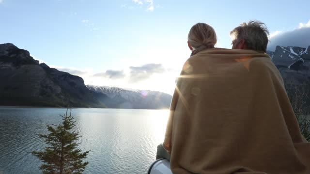 vídeos de stock, filmes e b-roll de casal relaxa no capô do veículo/ táxi ao nascer do sol - água parada