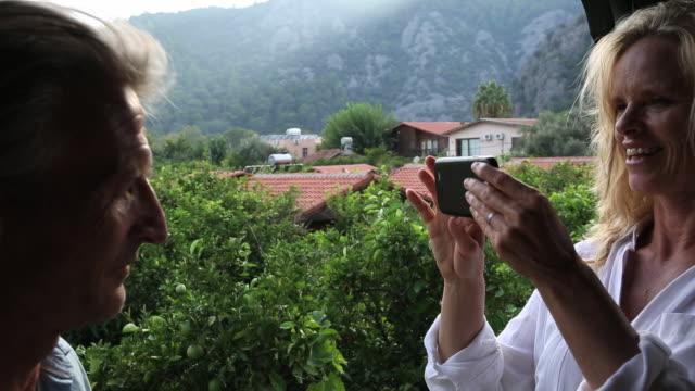 Couple relax on veranda, take smart phone pic across jungle canopy