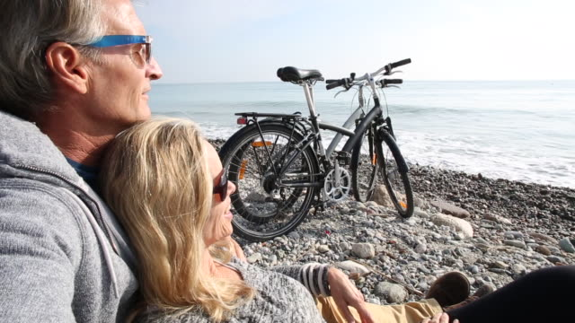 Couple relax with bikes on pebble beach, surf behind
