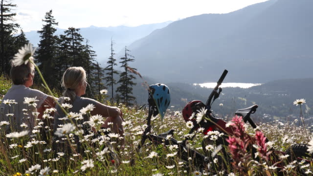 couple relax with mountain bikes on meadow slope, in flowers - british columbia stock videos & royalty-free footage
