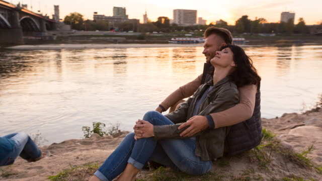 stockvideo's en b-roll-footage met ms couple relaxing at city beach at sunset - warschau