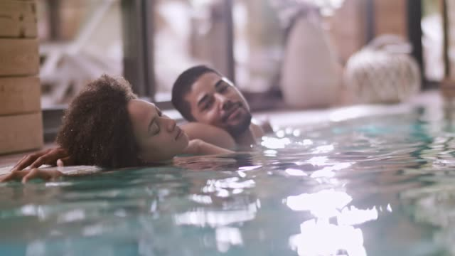 couple relaxing at healt spa pool - mid adult couple stock videos & royalty-free footage