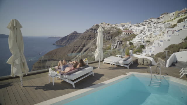 couple relaxing at swimming pool of luxury hotel in santorini - insel santorin stock-videos und b-roll-filmmaterial
