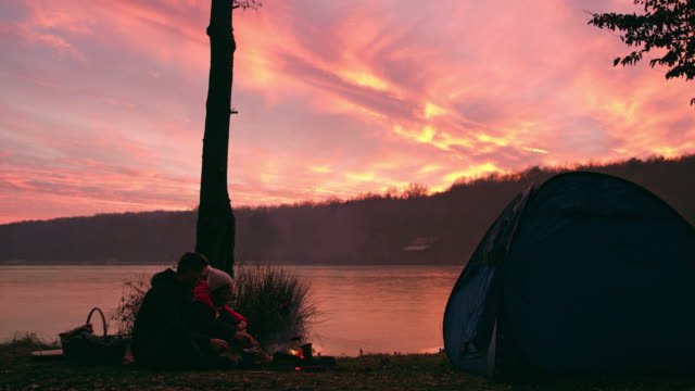 ms couple relaxing by campfire at tranquil autumn sunset lakeside,prekmurje,slovenia - prekmurje stock videos & royalty-free footage