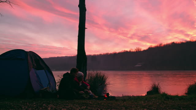 ms couple relaxing by campfire at tranquil,autumn sunset lakeside,prekmurje,slovenia - prekmurje stock videos & royalty-free footage