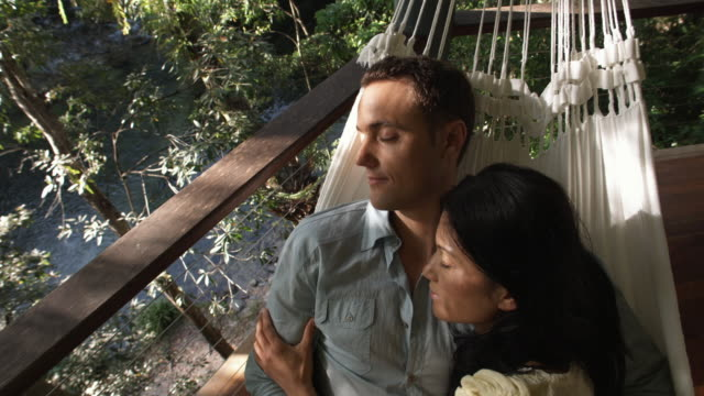 ha, cu, couple relaxing in hammock on balcony overlooking forest river, mossman, queensland, australia - hammock stock videos & royalty-free footage