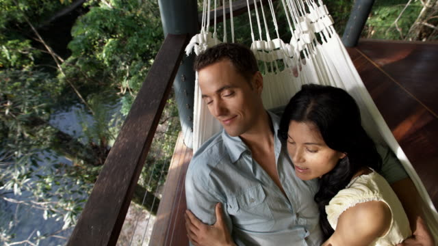 ha, cu, couple relaxing in hammock on balcony overlooking forest river, mossman, queensland, australia - lying down stock videos & royalty-free footage