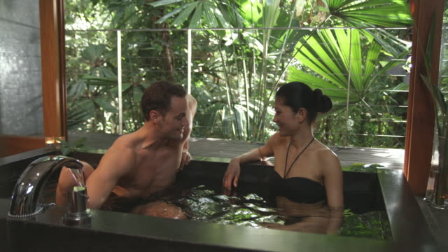 ms, couple relaxing in spa bath, mossman, queensland, australia - taking a bath stock videos and b-roll footage