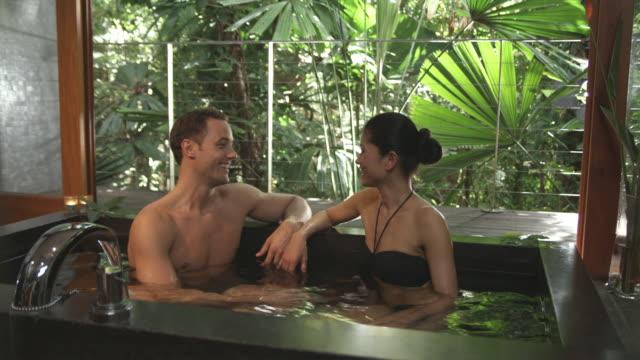 ms, couple relaxing in spa bath, mossman, queensland, australia - ウチワヤシ点の映像素材/bロール