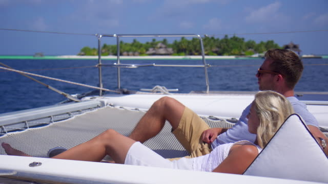 a couple relaxing on a boat at a tropical island resort hotel. - slow motion - tourist resort stock videos & royalty-free footage