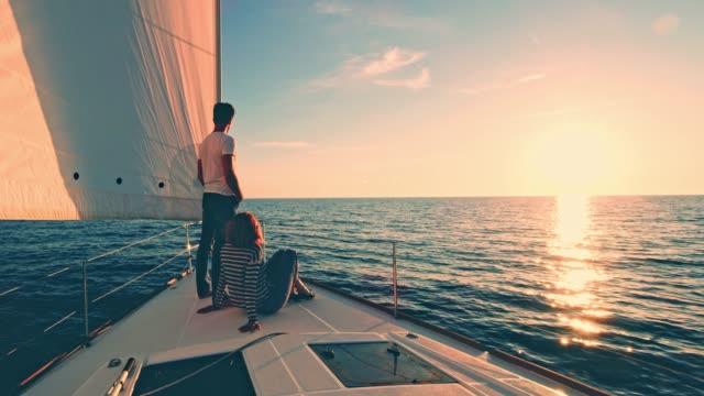 vídeos de stock e filmes b-roll de ws couple relaxing on a deck of a sailboat at sunset - veleiro