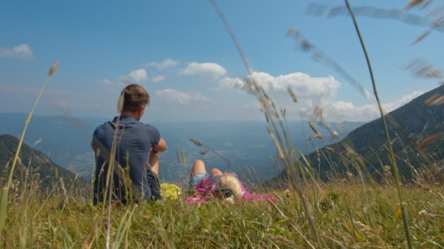 slo mo couple relaxing on a mountain hill - mid adult couple stock videos & royalty-free footage