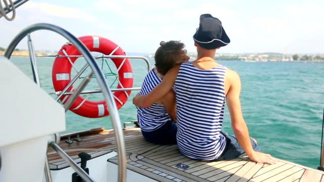 vidéos et rushes de couple de détente sur un bateau à voile - équipe de voile