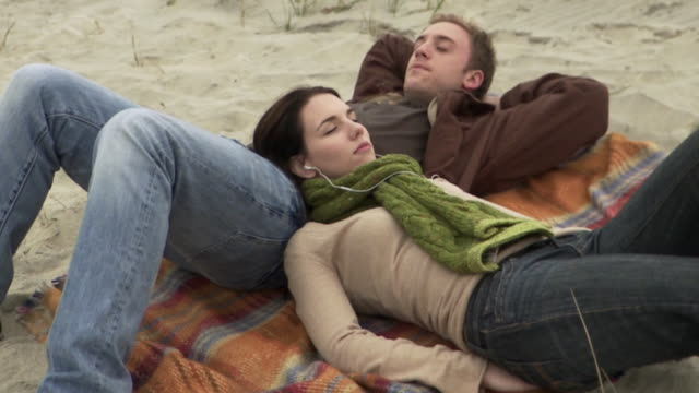 MS HA Couple relaxing on blanket on beach, listening to music and talking / Sea bright, New Jersey, USA