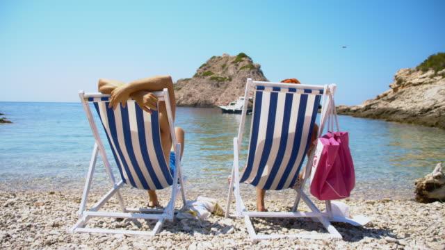 vídeos de stock e filmes b-roll de casal relaxante na praia paradisíaca - apanhar sol