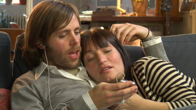 cu, couple relaxing on sofa, listening mp 3 player - wife sharing stock-videos und b-roll-filmmaterial
