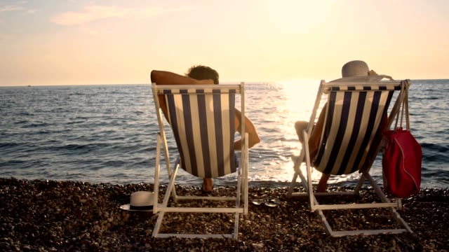 slo mo couple relaxing on the beach at sunset - outdoor chair stock videos & royalty-free footage