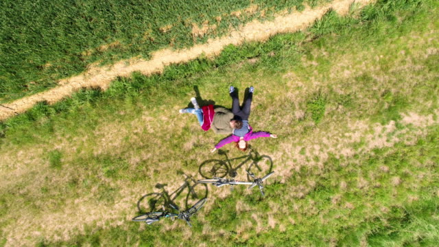 aerial couple relaxing on the grass - grass stock videos & royalty-free footage