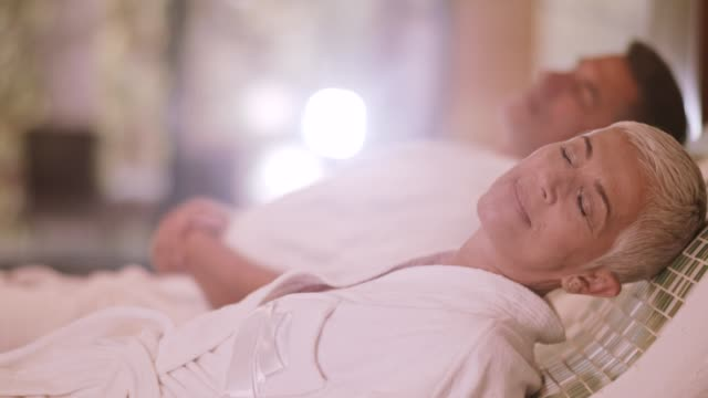 couple relaxing on warm tepidarium at the spa - spa treatment stock videos & royalty-free footage