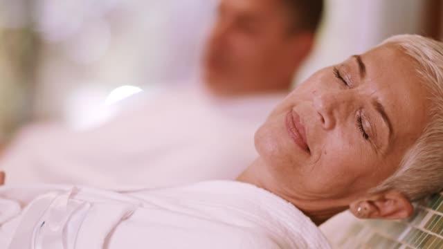 couple relaxing on warm tepidarium at the spa - bathrobe stock videos & royalty-free footage