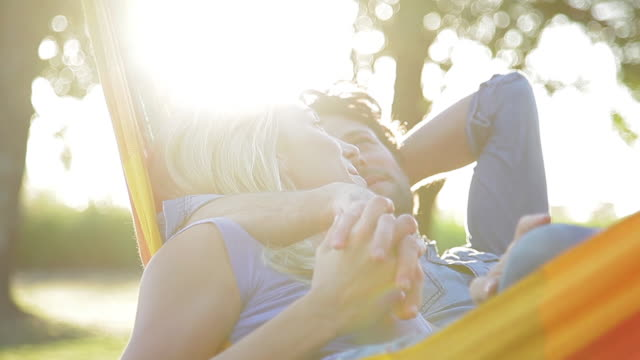 couple relaxing together in hammock - ehemann stock-videos und b-roll-filmmaterial
